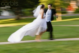 Bride and bridegroom running side by side
